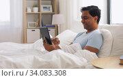 Купить «happy indian man with tablet pc in bed at home», видеоролик № 34083308, снято 1 июня 2020 г. (c) Syda Productions / Фотобанк Лори