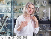 Woman chooses rose quartz jewelry in boutique. Стоковое фото, фотограф Яков Филимонов / Фотобанк Лори