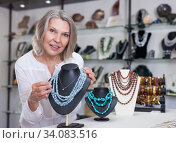 Adult woman chooses jewelry from turquoise jewelery in the store. Стоковое фото, фотограф Яков Филимонов / Фотобанк Лори