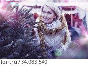 Mature female buying decoration and tree at Christmas Fair. Стоковое фото, фотограф Яков Филимонов / Фотобанк Лори