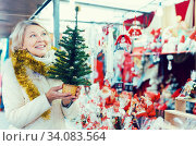 Portrait of mature female in tinsel choosing Christmas tree. Стоковое фото, фотограф Яков Филимонов / Фотобанк Лори