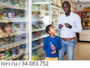 Купить «Young man and boy reading shopping list», фото № 34083752, снято 15 апреля 2019 г. (c) Яков Филимонов / Фотобанк Лори