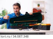 Купить «Young male repairman repairing violin», фото № 34087348, снято 25 октября 2019 г. (c) Elnur / Фотобанк Лори