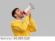 man in yellow sweatshirt shouting to megaphone. Стоковое фото, фотограф Syda Productions / Фотобанк Лори