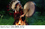 Female shaman in native American Indian headdress play the tambourine at night in the forest by the fire. Стоковое видео, видеограф Алексей Кузнецов / Фотобанк Лори