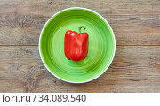 Red bell pepper on a green plate on a wooden tabletop. Стоковое фото, фотограф Евгений Харитонов / Фотобанк Лори
