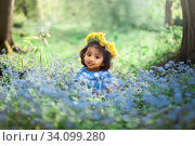 A small girl with dandelion wreath is sitting on field of forget me not blue flowers. Стоковое фото, фотограф Юлия Кузнецова / Фотобанк Лори