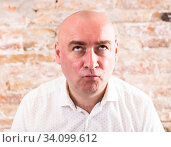 Купить «portrait of bald adult mature man with emotions against brick wall», фото № 34099612, снято 23 мая 2020 г. (c) Татьяна Яцевич / Фотобанк Лори