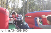 Emotional man tied with rope to his friend competing to collect hoops on inflatable ring. Стоковое видео, видеограф Яков Филимонов / Фотобанк Лори