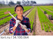 Smiling Latina standing on farm field with hoe. Стоковое фото, фотограф Яков Филимонов / Фотобанк Лори