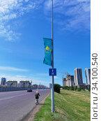 Купить «Астана, Казахстан - 2020.06.27: национальный флаг Казахстана на мачте освещения улицы», фото № 34100540, снято 28 июня 2020 г. (c) Максим Гулячик / Фотобанк Лори