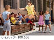 Energetic kids playing and skipping on elastic jumping rope in yard. Стоковое фото, фотограф Яков Филимонов / Фотобанк Лори