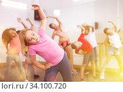 Купить «Girl exercising in group during dance class», фото № 34100720, снято 15 июля 2020 г. (c) Яков Филимонов / Фотобанк Лори
