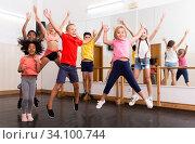 Cheerful tweens jumping with trainer during dance class. Стоковое фото, фотограф Яков Филимонов / Фотобанк Лори