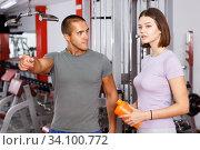 Купить «Instructor helping young woman with exercise», фото № 34100772, снято 15 октября 2018 г. (c) Яков Филимонов / Фотобанк Лори