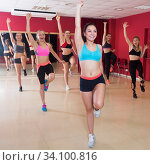 Купить «Young smiling females practicing zumba in class», фото № 34100816, снято 31 мая 2017 г. (c) Яков Филимонов / Фотобанк Лори