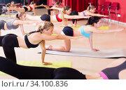 Купить «women perform exercises on yoga lying on mat», фото № 34100836, снято 31 мая 2017 г. (c) Яков Филимонов / Фотобанк Лори
