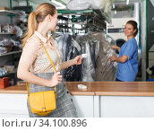 Купить «Woman receiving clothes after dry cleaner», фото № 34100896, снято 9 мая 2018 г. (c) Яков Филимонов / Фотобанк Лори