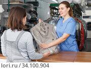 Купить «Worker of dry cleaner returning clean clothes», фото № 34100904, снято 9 мая 2018 г. (c) Яков Филимонов / Фотобанк Лори