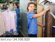 Купить «Portrait of girl laundry worker on background of garments racks at dry cleaner», фото № 34100920, снято 9 мая 2018 г. (c) Яков Филимонов / Фотобанк Лори