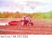 Купить «Russia Samara May 2020: Spring. Sowing work. A tractor with a seeder trailer works in the field at sunset.», фото № 34101032, снято 11 мая 2020 г. (c) Акиньшин Владимир / Фотобанк Лори