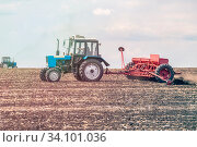 Купить «Russia Samara May 2020: Spring. Sowing work. A tractor with a seeder trailer works in the field at sunset.», фото № 34101036, снято 11 мая 2020 г. (c) Акиньшин Владимир / Фотобанк Лори