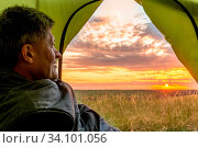 Купить «A mature man peeks out of a tourist tent and admires the picturesque sunset of the day.», фото № 34101056, снято 12 мая 2020 г. (c) Акиньшин Владимир / Фотобанк Лори