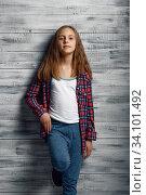 Купить «Adorable little girl standing at wall in studio», фото № 34101492, снято 9 июня 2020 г. (c) Tryapitsyn Sergiy / Фотобанк Лори