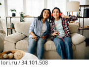 Купить «Two women in headphones listening to music on sofa», фото № 34101508, снято 20 июня 2020 г. (c) Tryapitsyn Sergiy / Фотобанк Лори