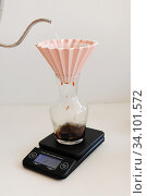 Coffee brewing in origami dripper on electronic scale. Стоковое фото, фотограф Кристина Сорокина / Фотобанк Лори