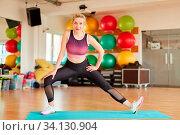 Junge Frau macht eine Stretching Übung für die Beine auf der Yogamatte. Стоковое фото, фотограф Zoonar.com/Robert Kneschke / age Fotostock / Фотобанк Лори