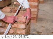 Handwerker mauert Ziegelwand mit Hilfe einer Maurerkelle und Zollstock - Nahaufnahme. Стоковое фото, фотограф Zoonar.com/Alfred Hofer / easy Fotostock / Фотобанк Лори