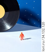 Купить «Plastic toy of spaceman on a light surface against blue sky background with stars and black vinyl record as a planet , hard shadows, place for text. Outer space concept.», фото № 34132120, снято 5 июля 2020 г. (c) easy Fotostock / Фотобанк Лори