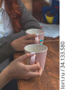 Купить «Two female teenagers drinking coffee at cafe restaurant with cup of espresso hot cappuccino on dating. Concept of female hands love and coffee. Italian delicious caffeine drink aroma latte», фото № 34133580, снято 10 июля 2020 г. (c) easy Fotostock / Фотобанк Лори