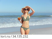 Купить «Woman with coconut cocktail standing on the beach», фото № 34135232, снято 25 февраля 2020 г. (c) Wavebreak Media / Фотобанк Лори