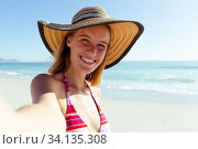Купить «Portrait of woman wearing hat smiling on the beach», фото № 34135308, снято 25 февраля 2020 г. (c) Wavebreak Media / Фотобанк Лори