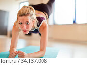 Junge Frau macht Gymnastik auf der Yoga Matte und streckt die Beine aus. Стоковое фото, фотограф Zoonar.com/Robert Kneschke / age Fotostock / Фотобанк Лори