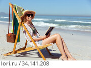 Купить «Woman reading a book while sitting on the beach», фото № 34141208, снято 25 февраля 2020 г. (c) Wavebreak Media / Фотобанк Лори