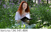Redheaded woman writes something and takes notes in notebook while sitting on a lawn among flowers in a city park. Стоковое видео, видеограф Алексей Кузнецов / Фотобанк Лори