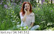 Купить «Young red-haired woman talking on a mobile phone among flowers in a city park», видеоролик № 34141512, снято 2 июля 2020 г. (c) Алексей Кузнецов / Фотобанк Лори