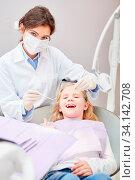 Zahnärztin mit Mundschutz bei der Vorsorge Untersuchung von einem kleinen Mädchen. Стоковое фото, фотограф Zoonar.com/Robert Kneschke / age Fotostock / Фотобанк Лори