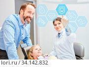 Zahnärztin zeigt Kind Auswahl an einem großen Touchscreen in der Zahnarztpraxis. Стоковое фото, фотограф Zoonar.com/Robert Kneschke / age Fotostock / Фотобанк Лори