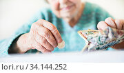 Купить «Detailed closeup photo of elderly 96 years old womans hands counting remaining coins from pension in her wallet after paying bills. Unsustainability of social transfers and pension system.», фото № 34144252, снято 6 июля 2020 г. (c) easy Fotostock / Фотобанк Лори