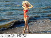 Купить «A girl in a white hat and in a red bathing suit stands on the seashore.», фото № 34145724, снято 3 июля 2020 г. (c) easy Fotostock / Фотобанк Лори