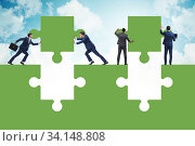 Купить «Businessman in teamwork concept with jigsaw puzzle», фото № 34148808, снято 9 июля 2020 г. (c) Elnur / Фотобанк Лори