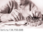 Купить «Detailed closeup photo of elderly 96 years old womans hands counting remaining coins from pension in her wallet after paying bills. Unsustainability of social transfers and pension system.», фото № 34150688, снято 4 июля 2020 г. (c) easy Fotostock / Фотобанк Лори