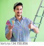 Купить «Young man contractor choosing color from rainbow», фото № 34150856, снято 2 мая 2018 г. (c) Elnur / Фотобанк Лори