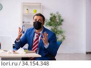 Купить «Sick male employee suffering at workplace from coronavirus», фото № 34154348, снято 15 февраля 2020 г. (c) Elnur / Фотобанк Лори