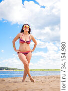 Beautiful mature woman with a luxurious body stands on the beach against the blue sky on a summer sunny day. Стоковое фото, фотограф Акиньшин Владимир / Фотобанк Лори