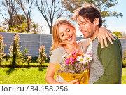Junge Frau und ihr Freund mit einem Blumenstrauß als Geschenk beim Rendezvous. Стоковое фото, фотограф Zoonar.com/Robert Kneschke / age Fotostock / Фотобанк Лори